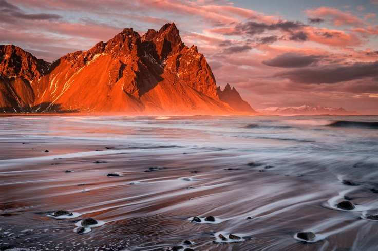 """Sunset at Stokksnes by Sophie Carr. Car says of this piece: """"Water trails on the beach at Stokksnes at sunset, with Vesturhorn illuminated by the setting sun."""" Photo taken in Iceland. Click here for more of the photographer's work!"""